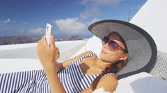 Woman Using Smart phone App Relaxing On Sofa Outdoor -  luxury resort - stock footage
