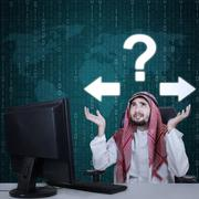 Frustrated Arabian worker and question mark - stock photo