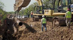 Two Track hoe's carry a long section of oil pipeline Stock Footage