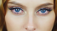 Piercing and gaze into the camera. Blue-eyed woman looking at the camera - stock footage