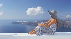 Luxury travel vacation woman looking at Santorini - famous tourist destination - stock footage