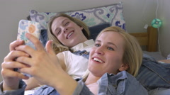 Girls Hang Out On Bed, Scroll Through Funny Photos On Phone(Steadicam Shot) - stock footage