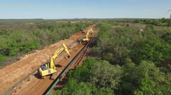 Aerial of a large oil pipeline under construction with two loaders Stock Footage