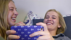 Girls Chill On Bed, They Watch Something Funny On A Smartphone - stock footage
