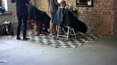 Two barbers working in street barbershop, providing haircuts for homeless people - stock footage
