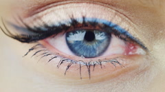 The eye of a young woman with blue eyes, looking directly - stock footage
