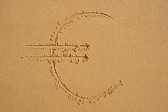 sign of EURO currency  drawn in the sand - stock photo