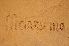 Marry Me Word Written On Sunny Beach Sand Stock Photos