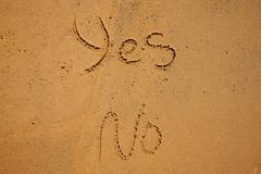 The words YES and NO written in beach sand - stock photo