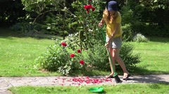 The girl with broom sweeping garden path covered with red rose petals. 4K - stock footage