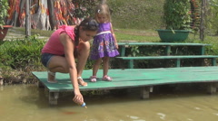 Woman and daughter feeding fishes in pond. the reserve walk geese. a lot of fish Stock Footage