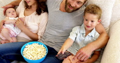 Family with pop corn on the couch Stock Footage