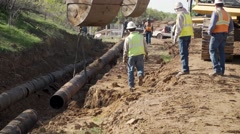 Construction workers setting an oil pipeline into trench Stock Footage