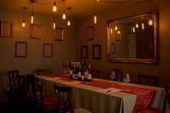 Long Table with Wine, Glasses, and Forms in Dimly-Lit Restaurant Stock Photos