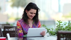 Woman with white tablet computer sits at a table in a cafe Stock Footage