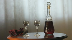 Hand pours a liqueur in wine glasses from a carafe Stock Footage