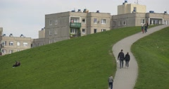 People Are Walking by Footpath Through Green Lawn Residential Houses on the Stock Footage