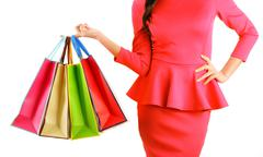 Woman's hand holding paper shopping bags isolated on white background - stock photo