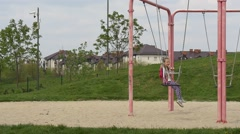 Sweet Girl Swinging on a Pink Swing. Stock Footage