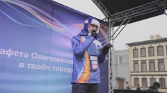Young man host in purple jacket, warm hat with microphone on stage. Concert - stock footage