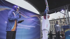Relay race Sochi Olympic torch in Saint Petersburg. Host on stage. Torchbearer Stock Footage