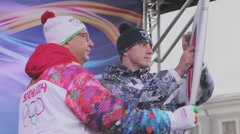 Relay race Sochi Olympic torch in Saint Petersburg. Torchbearer burn flame on Stock Footage