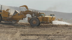 Earthmover and water truck crossing paths - stock footage