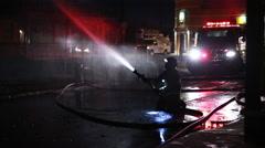 Firemen use hose in shadow Stock Footage