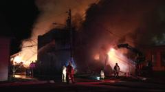 Excavator to demolishing intense burning home Stock Footage