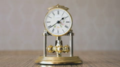 Clock with a pendulum in a form of rotating balls - stock footage