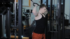The man trains his shoulders at the gym - stock footage