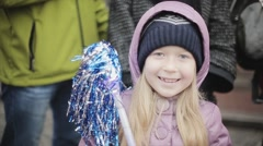 Little blonde smiling girl waving blue pom pom in camera. People. Sport event Stock Footage