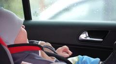 Footage mom takes son from the child seat of the car Stock Footage