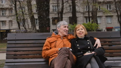Sweet mature couple relaxing on a bench and talking Stock Footage