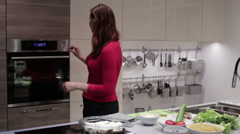 The woman puts the dish in the oven Stock Footage