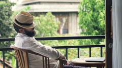 Young man with hat sleeping on chair on terrace  Stock Footage