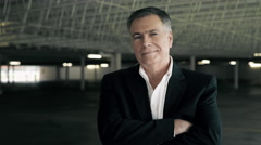 Businessman standing in a parking garage smiles at camera 4k Stock Footage