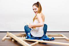 Woman assembling wooden furniture. DIY. Rear view. - stock photo