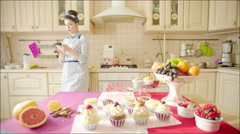 Woman cheking whether cakes are ready in the oven - stock footage