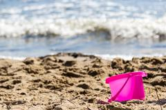 Small sand pail toy on summer beach. - stock photo