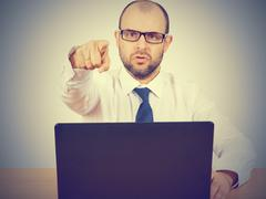 Angry  businessman sitting at his desk - stock photo