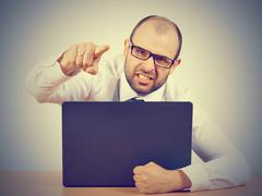 Angry  businessman sitting at his desk and screaming Stock Photos
