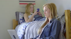 PStudent Works On Her Laptop, Her Roommate Relaxes And Plays On Her Smartphone Stock Footage