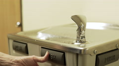 Businesswoman at a office drinking fountain getting water 4k Stock Footage