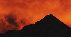 Clouds racing across a peak in orange sunlight Stock Footage