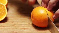 Chef Slices an Orange on a Bamboo Cutting Board Stock Footage
