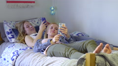 Girls Hang Out And Relax In Bed, They Check Their Smartphones And Interact Stock Footage