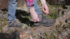 Safety first - Female hiker stopping to tie shoelaces Stock Footage