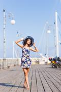 Travel tourism and people concept. Young woman with hat standing near boats in Stock Photos