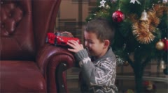 Little boy is playing with the toy car near the Christmas tree Stock Footage